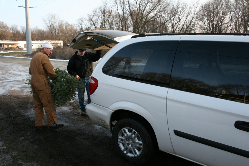 Christmas tree vendor Ken Mueller helps my husband, Randy, load our old-fashioned Christmas tree into our van.
