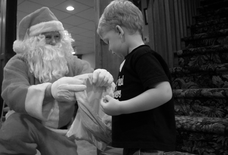 My great nephew, Hank, age 2 1/2, picks candy from Santa's bag at the Kletscher family Christmas.