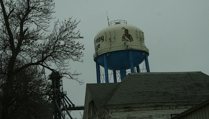A passing shot shows Chief Sleepy Eye's image painted on the water tower.
