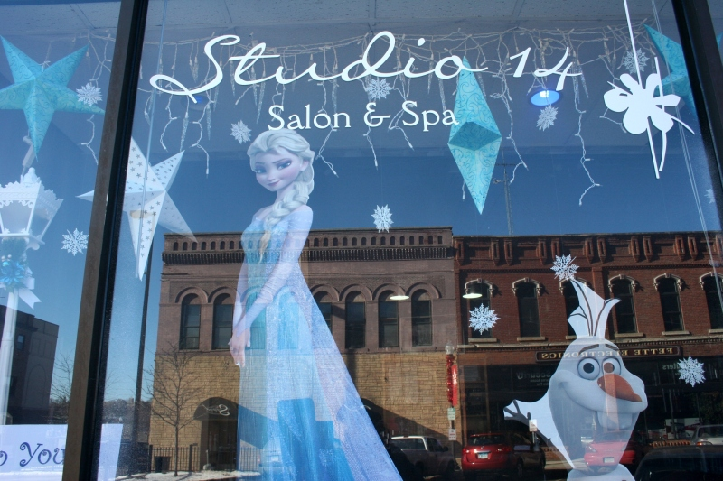 "Historic buildings are reflected in the windows of Studio 14 Salon and Spa at 204 Central Avenue North. The salon created a ""Frozen"" display for a downtown holiday decorating contest."