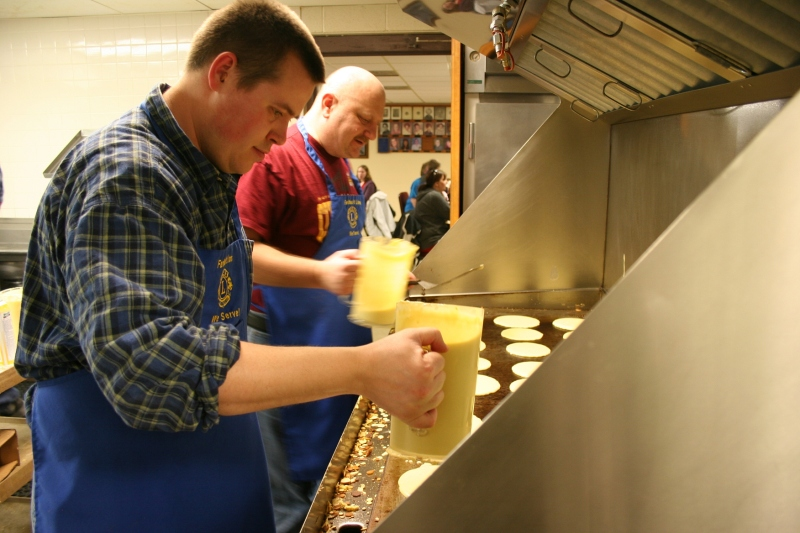 The volunteer on the right makes pancakes for the first time at the breakfast.