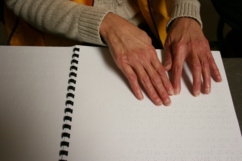 A visually-impaired volunteer reads a book in Braille while working at the breakfast. The Faribault Lions have funded many projects for the visually-impaired and were collecting used eyeglasses at the breakfast.