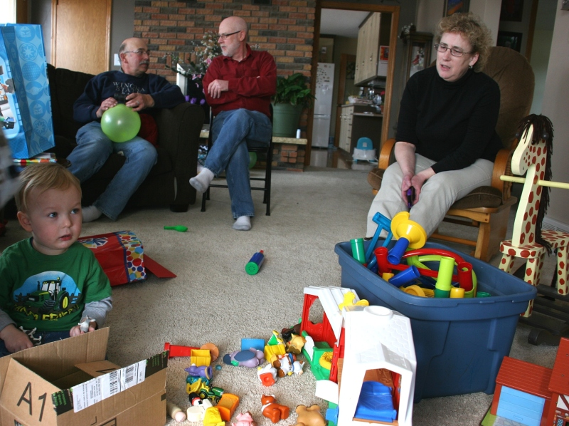 Landson opens gifts while his grandparents, left and right, and great uncle (my husband), middle watch.