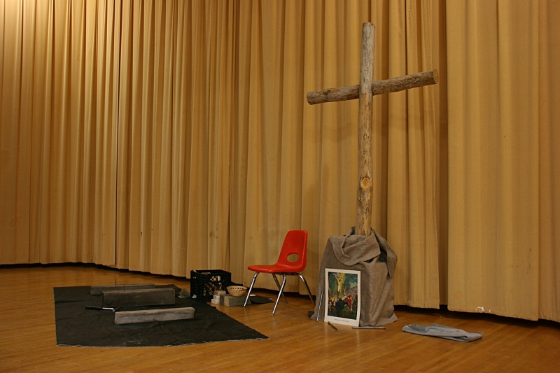 The stage was set with a cross, hammer and nails. Participants pounded nails into wood. Christ was nailed to the cross.