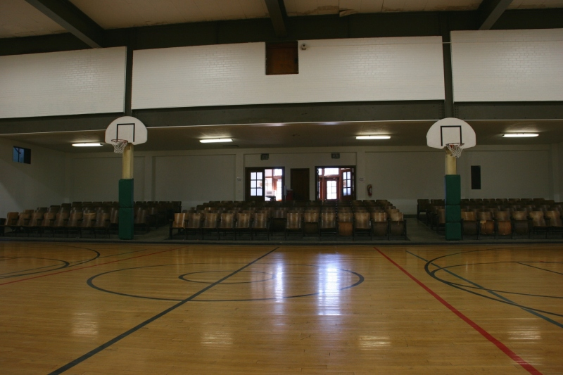 Looking across the gym floor toward the original fold-up chairs and the entry into the auditorium.