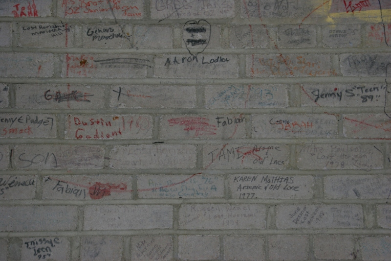 Students involved in theatrical productions signed the stage wall behind the stage curtain.