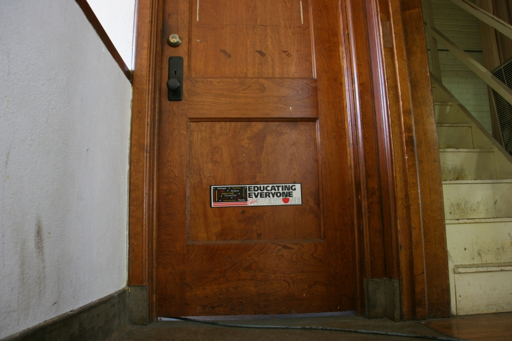 "A sticker, ""Educating Everyone Takes Everyone,"" on a sturdy wood door reminds visitors of this structure's original purpose."