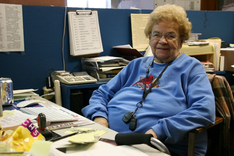 Janis Ray sits at the desk in a former classroom turned office space.