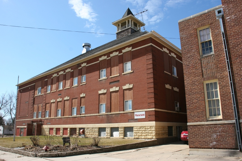 The 1902/1914 school is on the left, the 1936 gym on the right. Museum left, community center right. To enter, use the door between the buildings, in the area where the red car is parked in this photo.