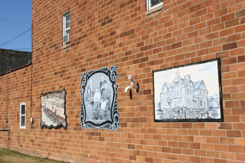 Murals grace the sides of two brick buildings sandwiching a vacant lot that is now a downtown mini park.