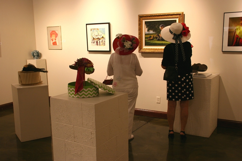 Attendees view the hat-themed exhibit in the gallery.
