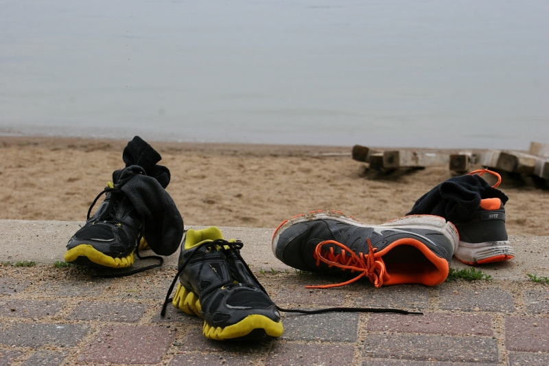 Teens' shoes abandoned along the brick pathway by the public beach.