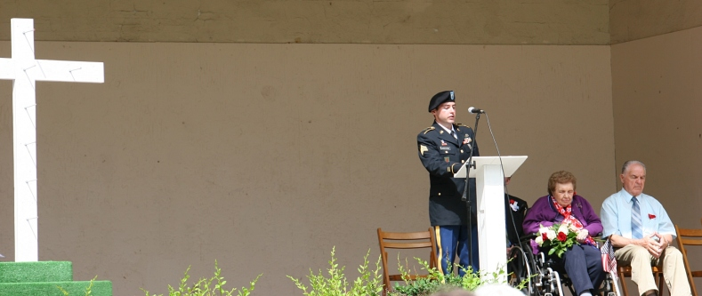 Honored combat veteran David Kirkpatrick address the crowd as grand marshalls Jean and Adrian Gillen watch.