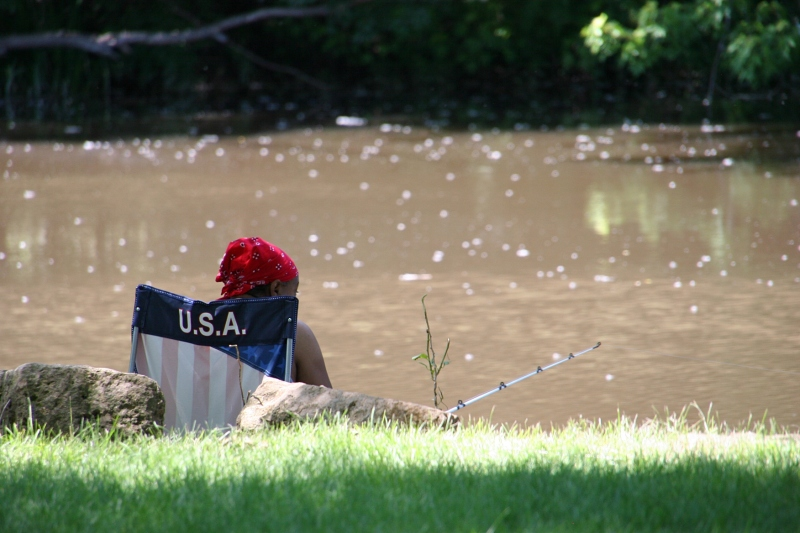 On a beautiful summer afternoon, a woman fishes the Straight River.