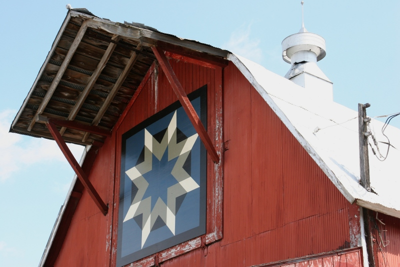 The barn quilt adds an artistic touch to this vintage barn.