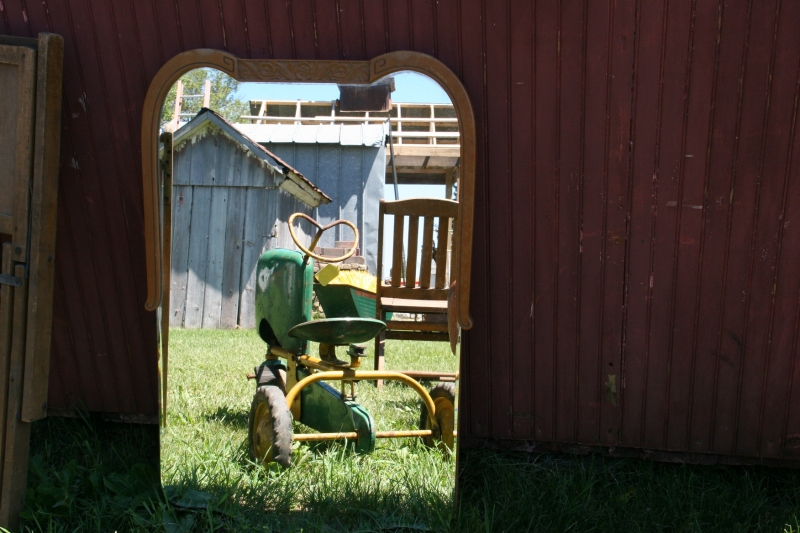 Several pedal tractors were for sale, including this one reflected in a mirror.