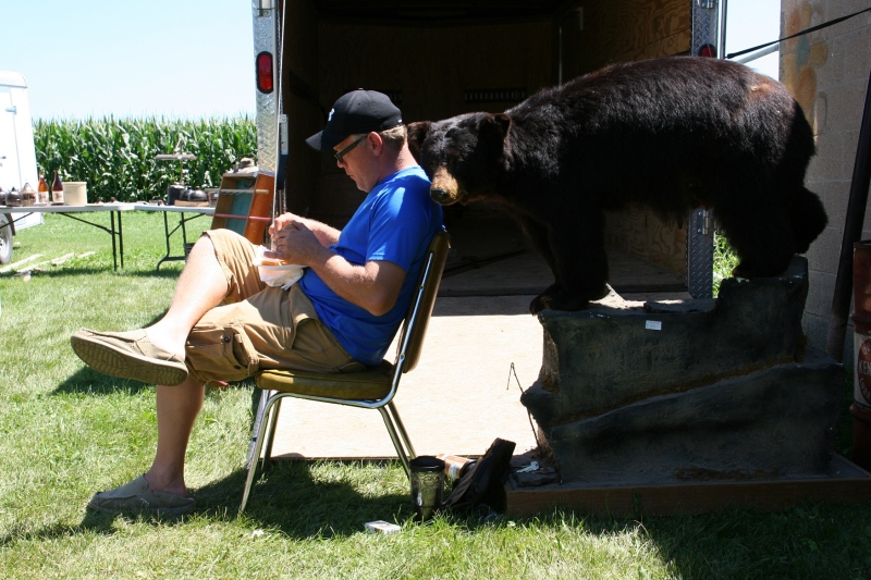 A vendor grabs lunch and settles in next to a bear he's selling.