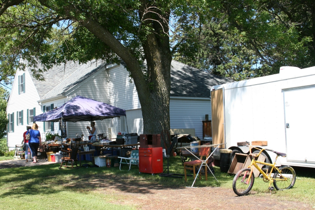 A vendor set up under the shade trees by the house.