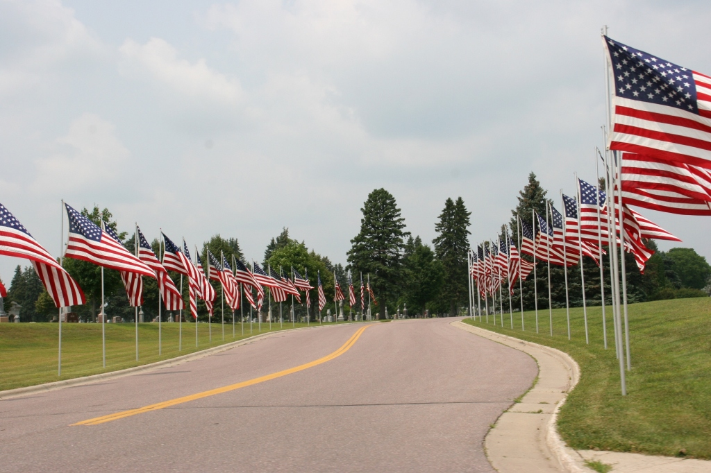 Flags line a cemetery entry along U.S. Highway 14 in New Ulm Saturday afternoon.