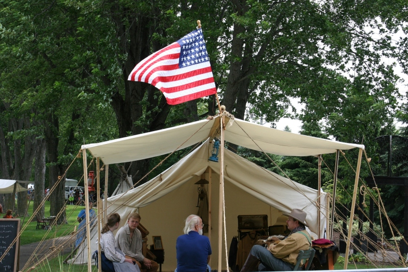 Sunday afternoon in Elysian, a flag flies over a tent on the Trails of History event.