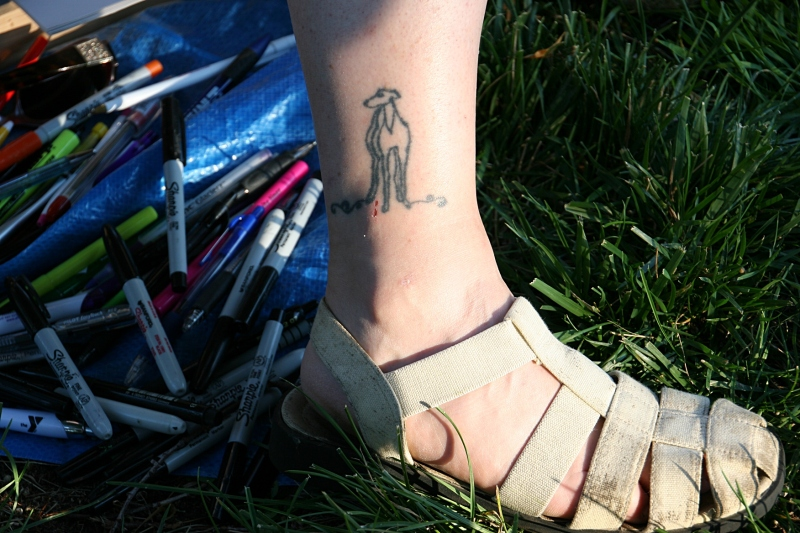 Tami's tools lie at her feet. Years ago, Tami designed the greyhound tatoo inked onto her leg in Vegas.