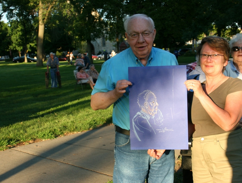 A concert goer poses with a caricature created by Irina Mikhaylova.