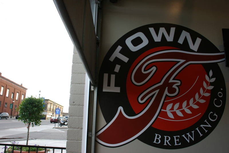 A logo on the taproom wall, which opens to a street-side patio. To the left in the photo, up the hill, is Central Avenue. That