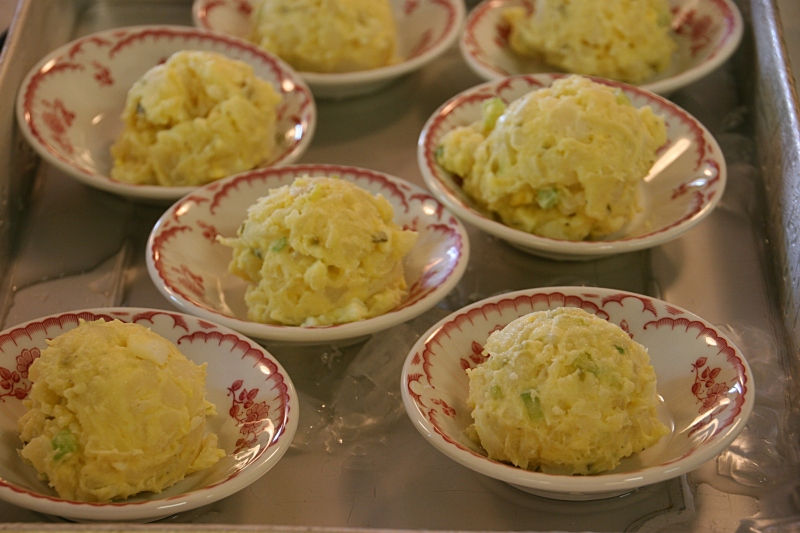 Scooped potato salad on ice, ready to go.