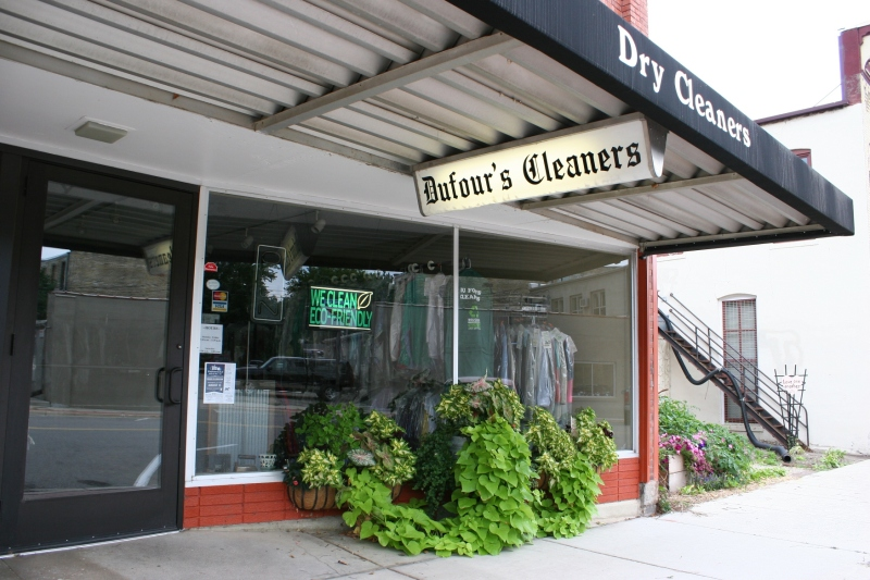 Beautiful flowers and plants spill from containers at Dufour's Cleaners next to the garden.
