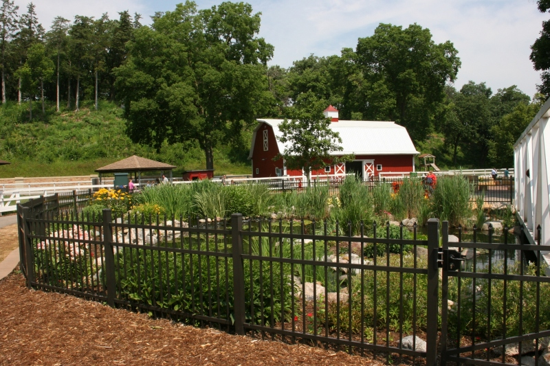 A fenced pond is in the foreground and a second barn type pole shed in the background.
