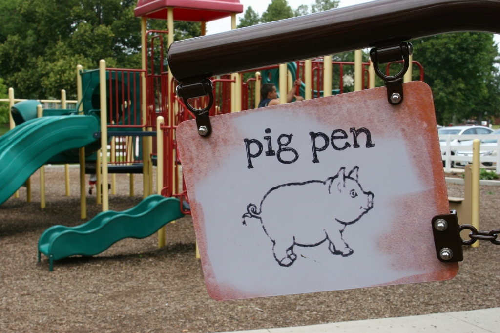 Love the signage at the farm-themed playground. There's also traditional playground equipment, background.
