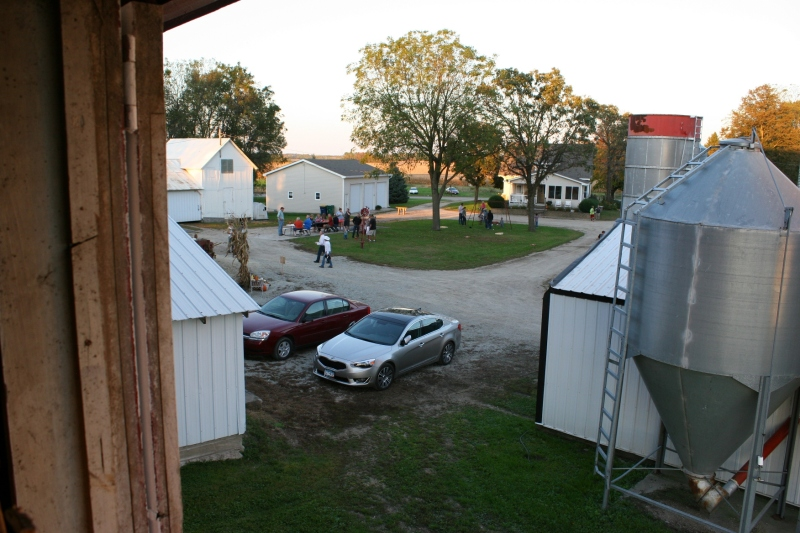 A view of the farmyard and barn dance guests from a hayloft window.