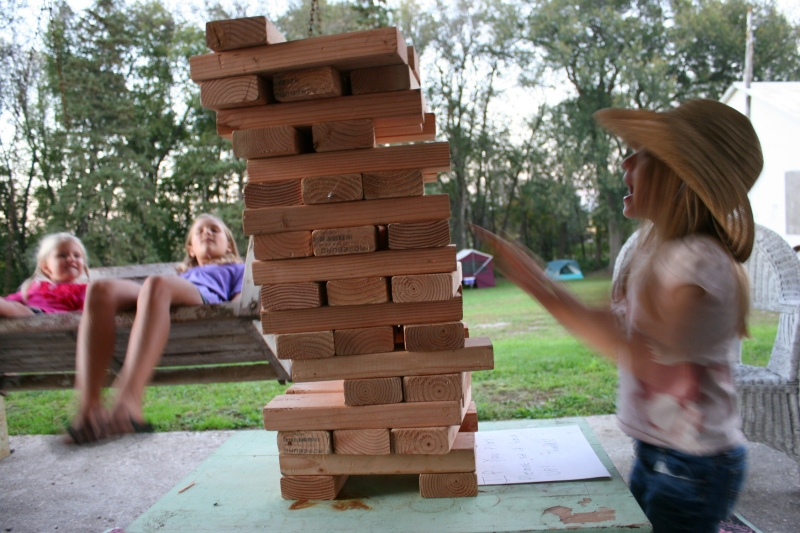 While two girls sway on a swing, another builds blocks.