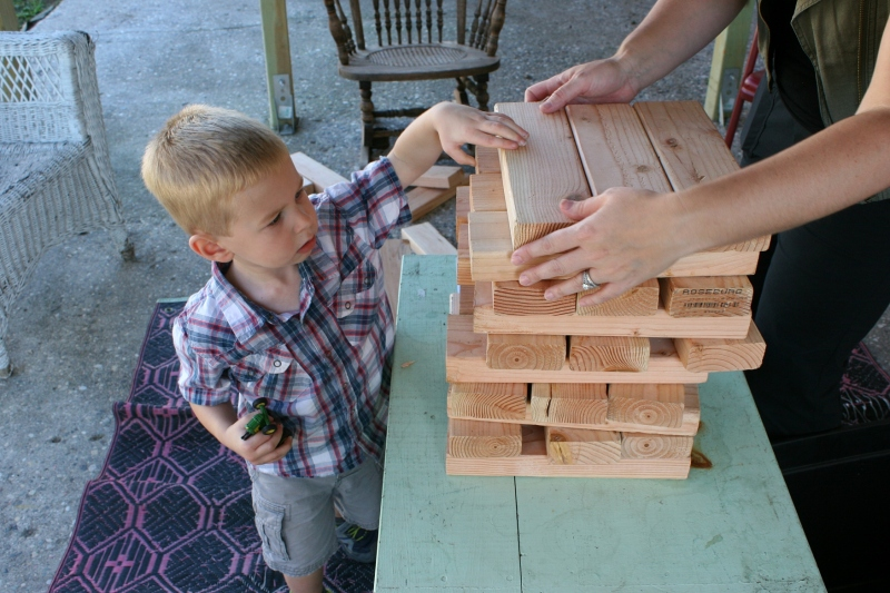 This little guy wouldn't even set down his toy John Deere tractor to stack over-sized Jenga blocks.