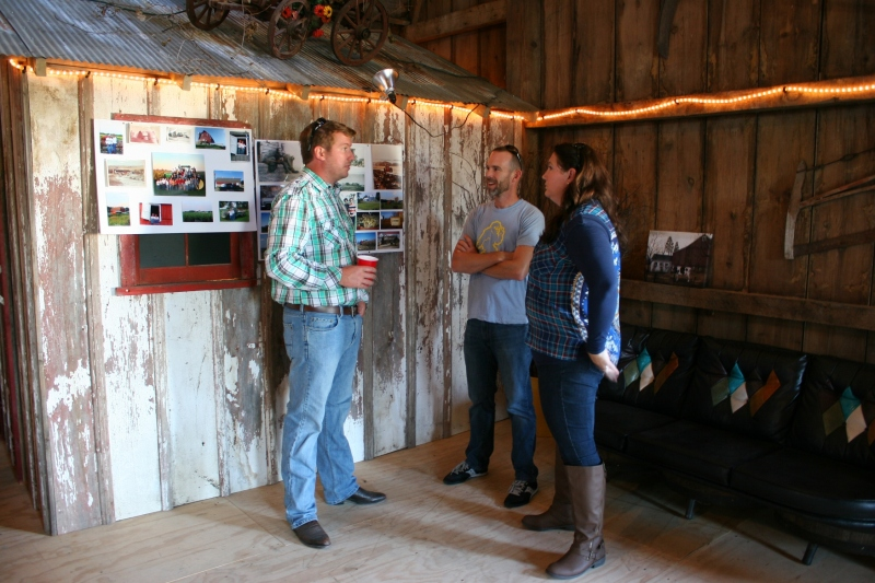 Guests gather in a corner near a display of Becker family farm photos.