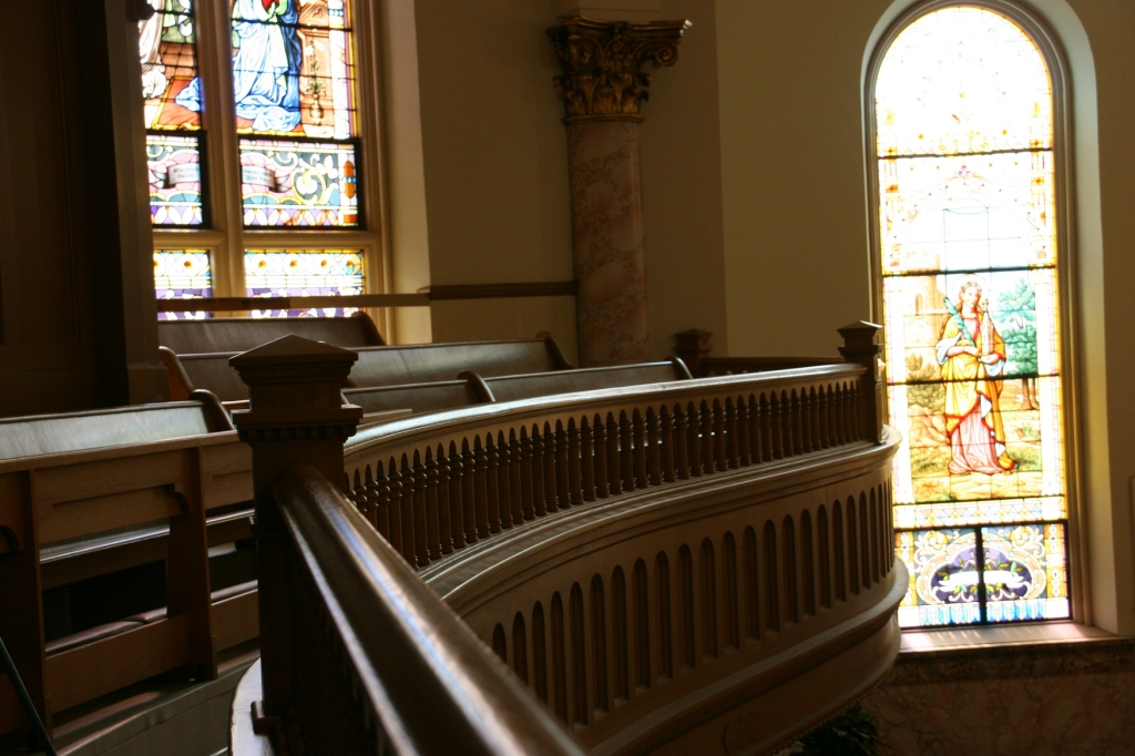 Beautiful morning light filters through stained glass onto the curving balcony railing.