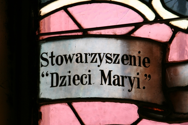 Polish words on a stained glass window translate to