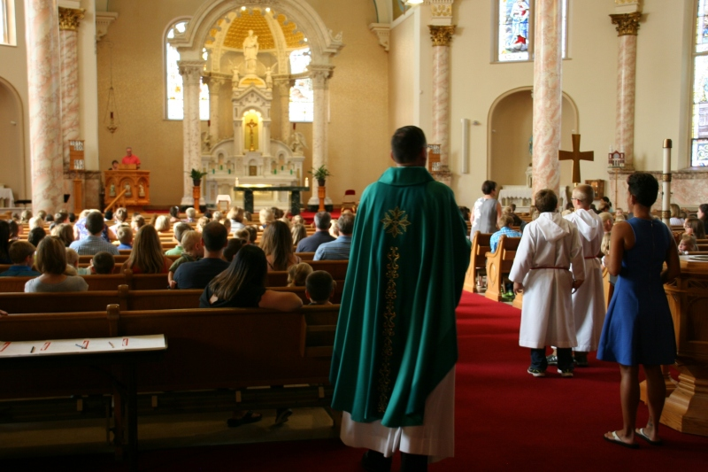 The priest is about to proceed up the aisle to begin Mass.