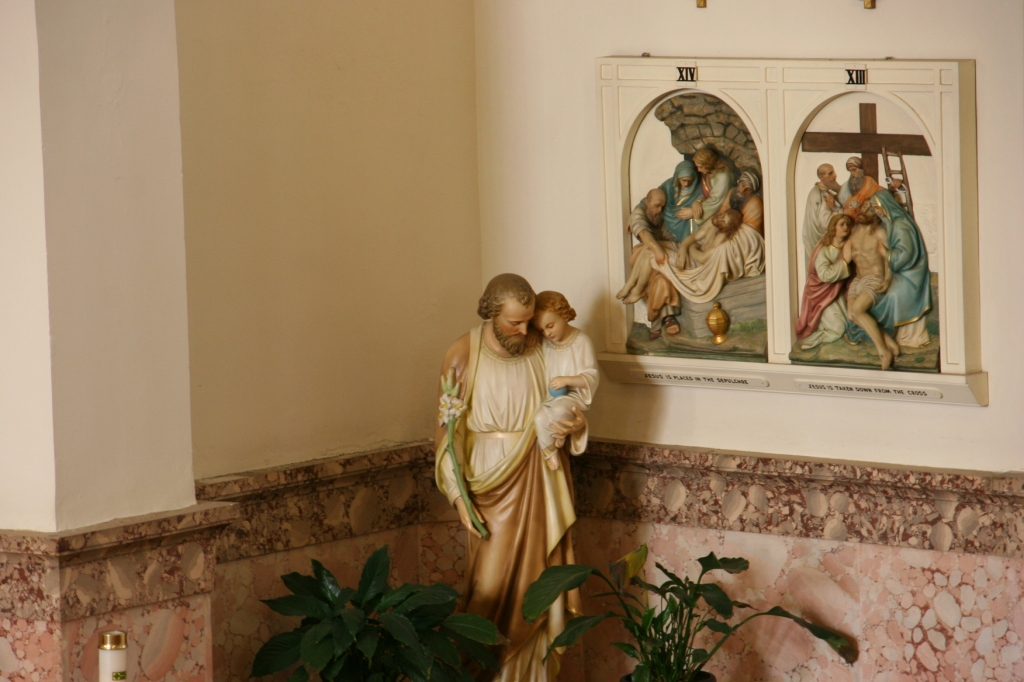 A statue is tucked into a corner below stations of the cross.