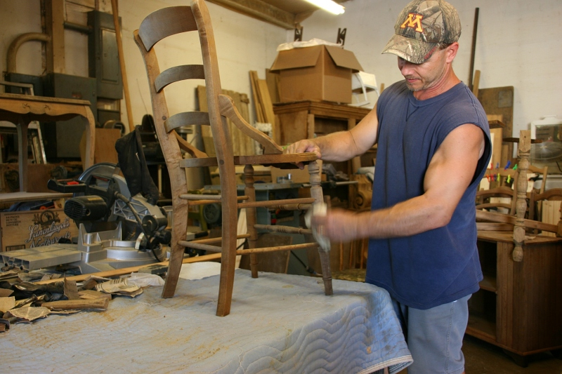Jeff Lerum sands a chair in his shop, where he restores and repairs furniture.