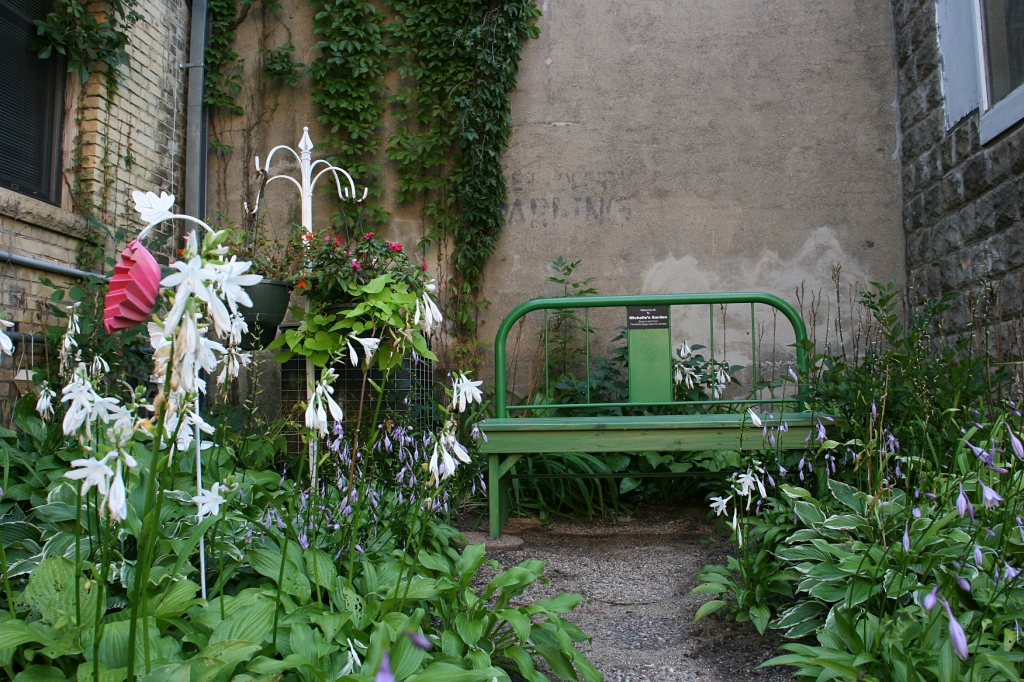 Open the gate and follow the hosta lined path to a bench.
