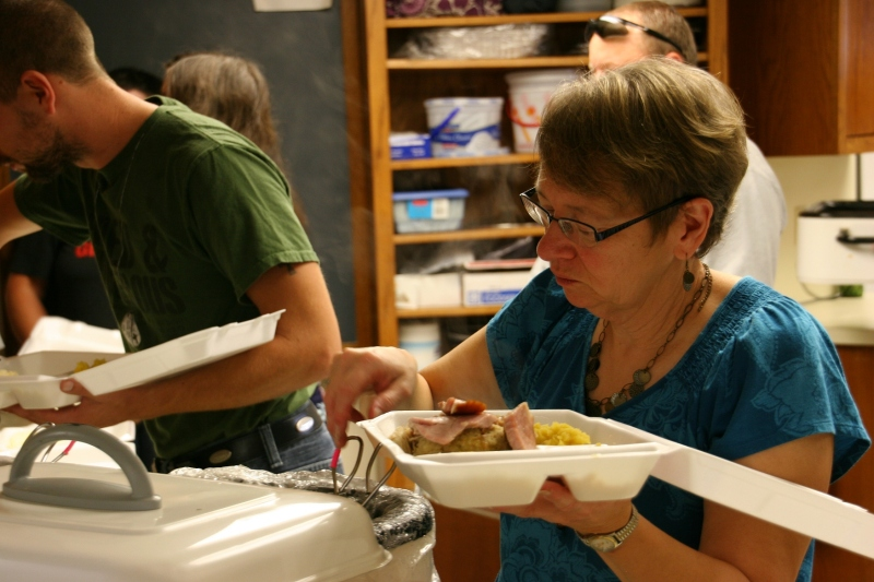 A member of the kitchen crew dishes up meals for take-out.