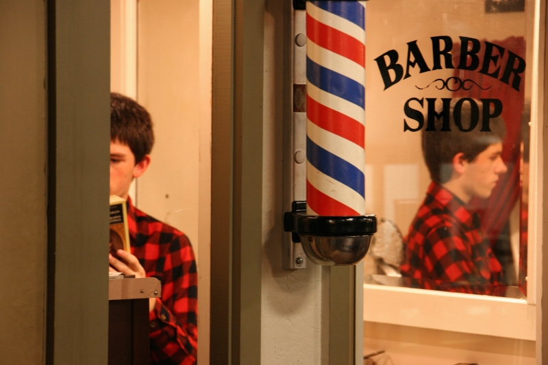A high school reenactor reads a book in the museum barbershop.