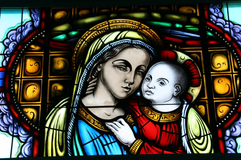 The stained glass windows inside the Mother of Good Cunsel Votive Chapel depict apparitions and titles of Our Blessed Mother.