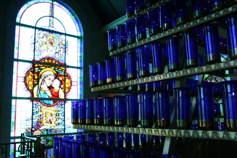 A rack holds 576 candles inside the Mother of Good Counsel Votive Chapel. Pilgrims, for a price, may have a candle lit. A lift allows lighting of the tiered candles stretching high into the chapel.