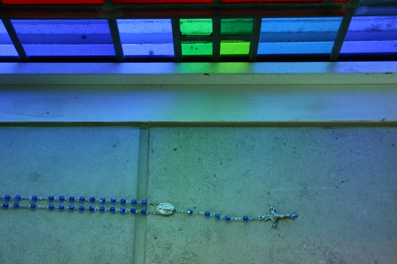 Rosary beads on a chapel window sill.