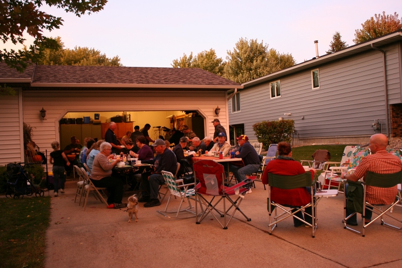 As the sun sets in southern Minnesota, guests gather on the driveway and in the garage to sample soups and chili.
