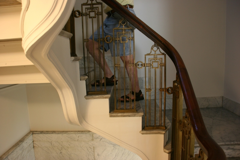 Mahogany railings wrap the white marble staircase.