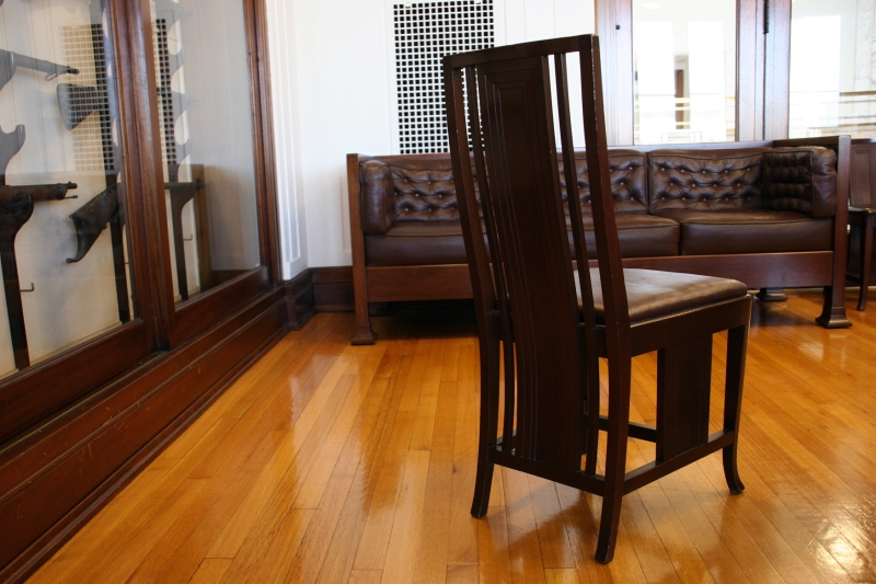 A Prairie School inspired chair in the boardroom, next to the gun collection.
