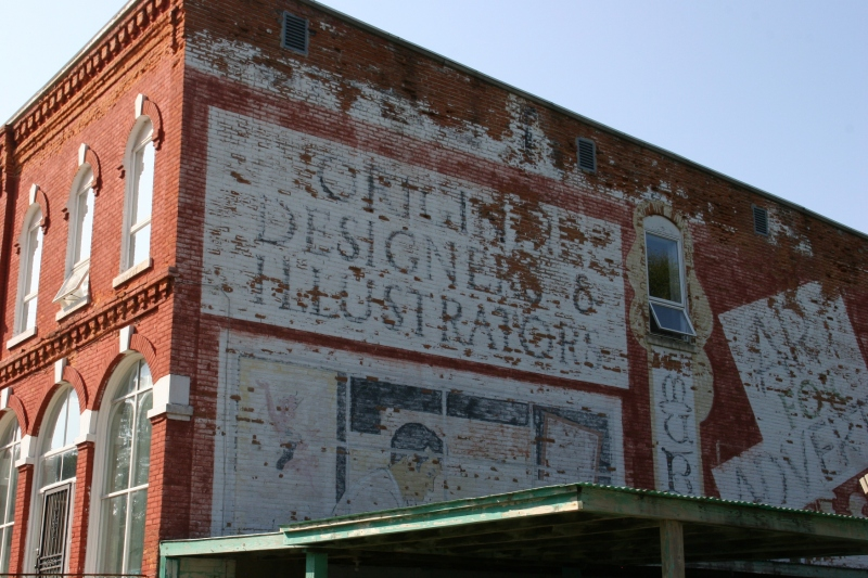 A mural on the east side of the building denotes this as an artist's haven. Cannot you decipher the first word for me?
